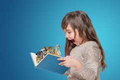Öppen bok för förvånat liten flickainnehav med djur Arkivbilder