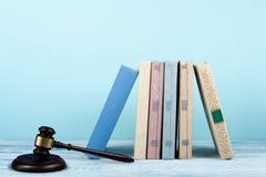 Öppen bok för lagbegrepp med trädomareauktionsklubban på tabellen i en rättssal eller ett rättsskipningkontor, blå bakgrund kopia Royaltyfri Fotografi