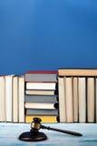 Öppen bok för lagbegrepp med trädomareauktionsklubban på tabellen i en rättssal eller ett rättsskipningkontor, blå bakgrund kopia Arkivbilder