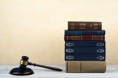 Öppen bok för lagbegrepp med trädomareauktionsklubban på tabellen i en rättssal eller ett rättsskipningkontor, gul beiga Royaltyfria Foton