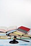 Öppen bok för lagbegrepp med trädomareauktionsklubban på tabellen i en rättssal eller ett rättsskipningkontor, vit bakgrund kopia Arkivbild