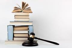 Öppen bok för lagbegrepp med trädomareauktionsklubban på tabellen i en rättssal eller ett rättsskipningkontor, vit bakgrund kopia Arkivfoto