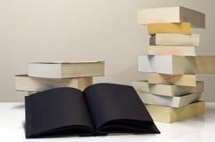 Öppen bok för svart i förgrund av två högar av böcker arkivbilder