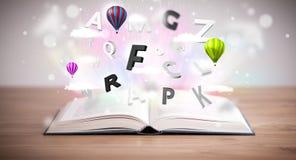 Öppen bok med att flyga bokstäver 3d på konkret bakgrund Arkivfoto