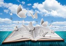 Öppen bok med fjärilsbokstäver på blå himmel arkivbilder