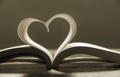 Öppen bok med sidor som bildar hjärtaform. arkivfoto