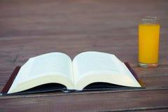 Öppen bok och en gul drink arkivfoto