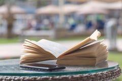 Öppen bok på en semesterhotelltabell royaltyfri bild