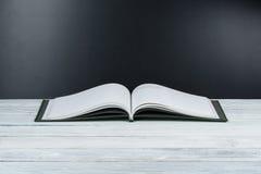 Öppen bok på trädäcktabellen och svart brädebakgrund tillbaka skola till Utbildningsbegrepp med kopieringsutrymme för din annons Royaltyfri Fotografi