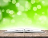 Öppen bok på wood plankor över defocused ljus bakgrund för abstrakt begreppgräsplan Arkivfoton