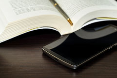 Öppen bok, penna och mobiltelefon på trätabellen Royaltyfri Fotografi
