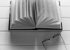 Öppen bok som är klar att läsa lögner på en vit trätabell bredvid de gamla runda exponeringsglasen royaltyfri fotografi