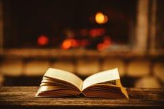 Öppen bok vid spisen med julprydnader Öppna berättelsen Arkivbilder