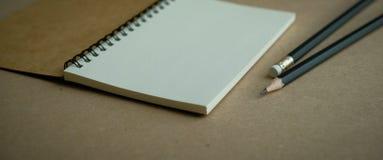 öppen brun spiralanteckningsbok med två blyertspennor Royaltyfri Foto