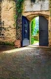 Öppen dörr i italiensk borggård Royaltyfri Foto