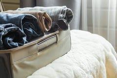 Öppen dörr och öppen resväska med kläder på sängen Arkivbild