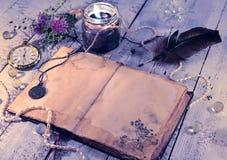Öppen dagbok med den gamla klockan, den svarta stearinljuset, vingpennan och medaljongen på plankor Arkivbilder