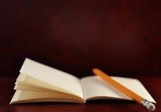 Öppen dagbokbok och blyertspenna på brun tappningbakgrund Royaltyfri Bild
