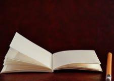 Öppen dagbokbok och blyertspenna på brun tappningbakgrund Royaltyfria Foton
