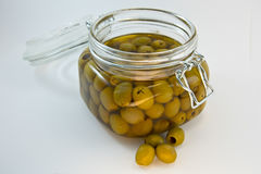 Öppen glass krus av oliv på vit bakgrund Arkivbild