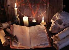 Öppen häxabok med papperssnirklar och ondskastearinljus mot pentagrambakgrund Royaltyfria Bilder