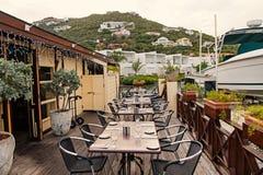 Öppen luft för restaurang i philipsburg, sint maarten Terrassera med tabeller, stolar och yachten i havet Äta och äta middag royaltyfria bilder