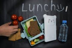 Öppen lunchask med en smörgås av helt kornbröd, ost, grön sallad, tomaten, gurkan och en flaska av vatten på en svart royaltyfria foton