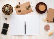 Öppen notepad för vit, kraft kuvert, kopp kaffe och kaktus i krukan som ligger på det beigea träskrivbordet, lekmanna- lägenhet,  royaltyfria bilder