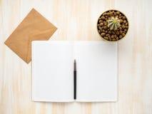 Öppen notepad för vit, kraft kuvert och kaktus i krukan som ligger på det beigea träskrivbordet, lekmanna- lägenhet, copyspace arkivbilder