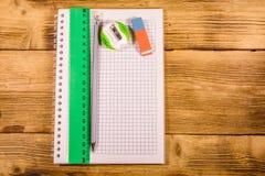 Öppen notepad, linjal och blyertspenna på en trätabell Top besk?dar arkivfoton