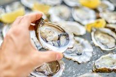 Öppen ostron i en manlig hand, mot bakgrunden av öppen oyste fotografering för bildbyråer