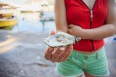 Öppen ostron i kvinnliga händer exotisk mat royaltyfria bilder
