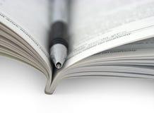 öppen penna för bok royaltyfria bilder