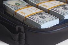 Öppen portfölj med hundra dollar räkningbuntar royaltyfri bild