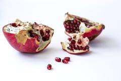 Öppen röd saftig granatäpplefrukt som isoleras på vit bakgrund som bakgrund är kan det använda julillustrationtemat Vinterfrukt p royaltyfri foto