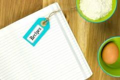 Öppen receptbok med matlagningingredienser Arkivbild