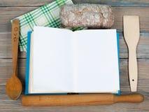 Öppen receptbok på träbakgrund, sked, kavel, grön rutig bordduk Arkivfoton