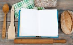 Öppen receptbok på träbakgrund, sked, kavel, grön rutig bordduk Royaltyfri Foto