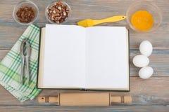 Öppen receptkockbok på träbakgrund, sked, kavel, rutig bordduk Royaltyfri Fotografi