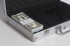 Öppen resväska med en miljon dollar räkningar med bandet royaltyfri fotografi