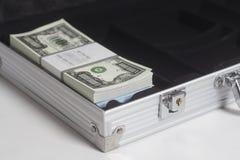 Öppen resväska med en miljon dollar räkningar med bandet royaltyfria foton