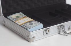Öppen resväska med hundra bunt för dollarräkningar royaltyfri bild