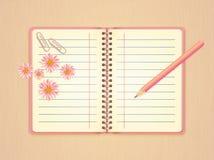 Öppen rosa anteckningsbok, blommor, paperclip och blyertspenna Arkivbild