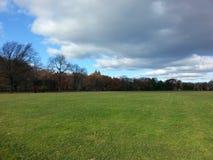 Öppen sikt av den stora gräsmattaCentral Park i höst med ett stort moln royaltyfri fotografi
