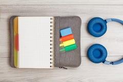 Öppen skrivbok på påse-blyertspenna fall med färgfiltpennor och markör, hörlurar på gråa träbräden arkivfoton