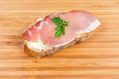 Öppen smörgås med kurerat griskött på bambuskärbrädan fotografering för bildbyråer