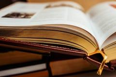 Öppen stor bok - folioark med guld- sidor tätt upp Begrepp om kunskap royaltyfria foton