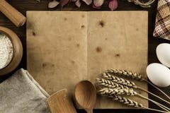Öppen tappningbok på den åldriga träbakgrunden Köksgeråd öron av vete, mjöl i en kruka hemlagat meny, recept, åtlöje Royaltyfri Foto