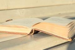 Öppen tappningbok på träbänk royaltyfri foto