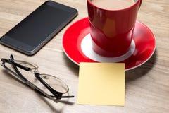 Öppen tom vit anteckningsbok, monokel, penna och kopp kaffe på skrivbordet arkivbilder